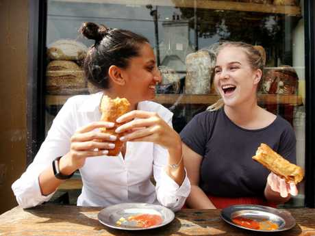 Tahra De Souza and Taylor Lynch enjoy a sausage roll each at the Bourke Street Bakery in Surry Hills — voted the No. 1 sausage roll in Wotif's People's Choice Awards. Picture: Tim Hunter