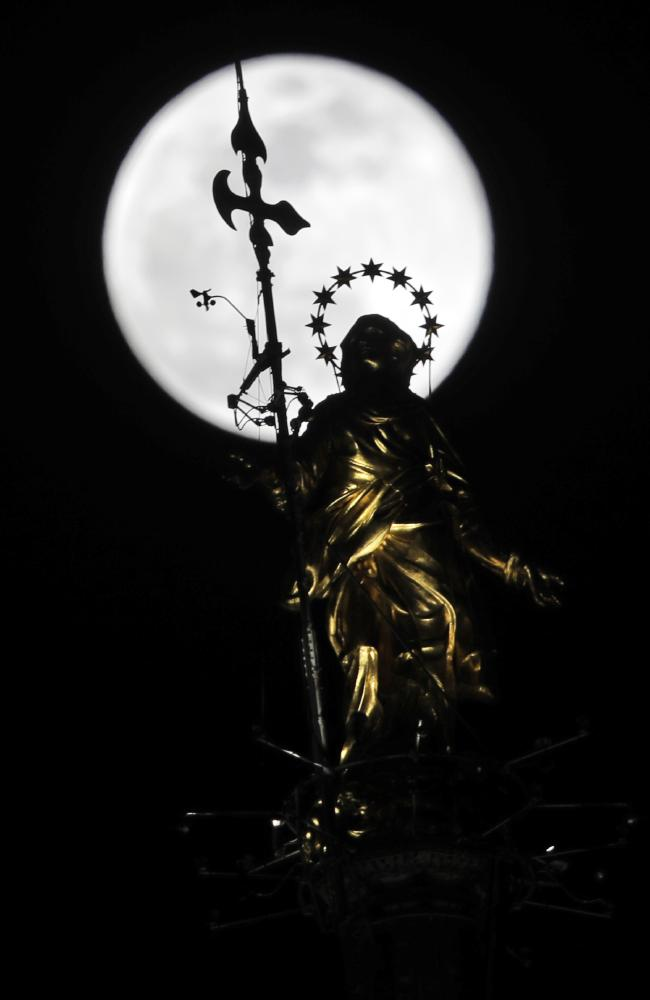 The full moon rises behind the statue of the