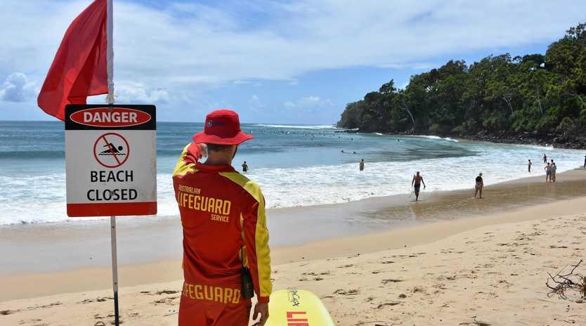 RARE: Lifeguard Jake McKellar watches over a closed Noosa Main Beach.