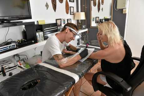 Ryan Steinbeck from The People's Ink, Yandina, working on a customers art work.