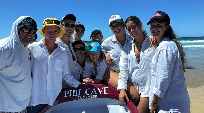 FITTING: The Noosa boaties with the surf boat named in Phil Cave's honour.