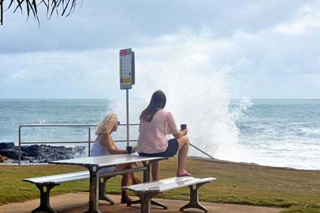 Onlookers watch on a high tide waves slam into rocks at Mooloolaba this morning.