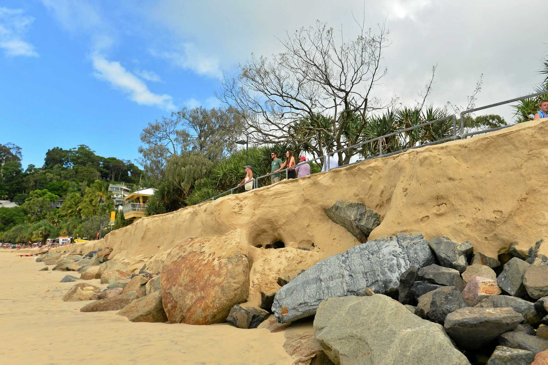 STORM surge has stripped metres of sand off Noosa's Main Beach, exposing the rock sea wall and raising fears water may inundate Hastings Street tomorrow.