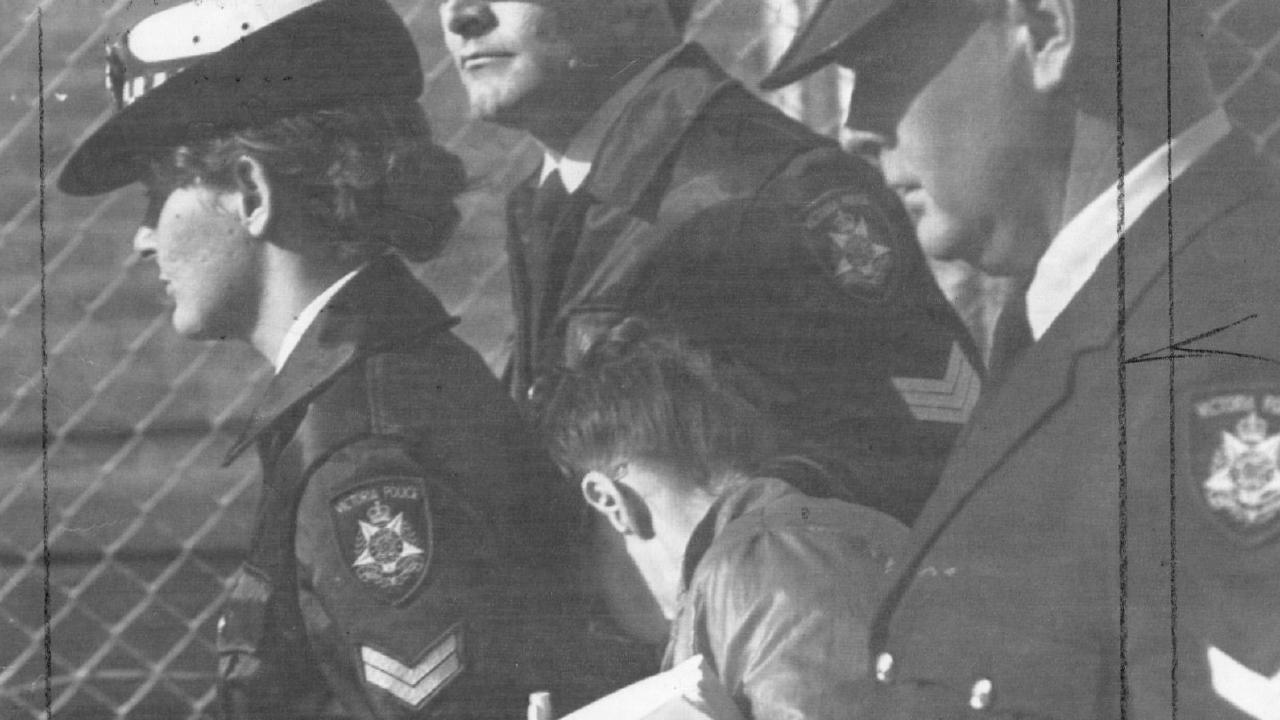 Judith Ip hides behind police as she is led into Mildura Magistrates' Court in 1988.