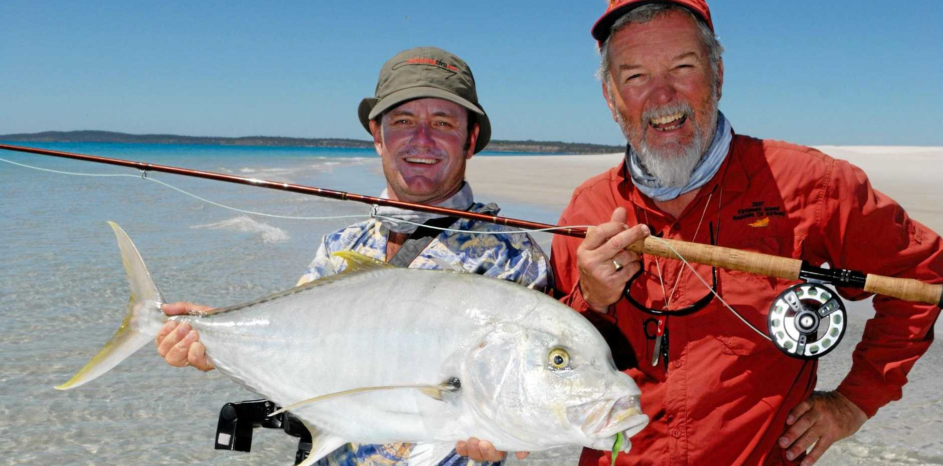 GLORY DAYS: Offshore Productions owner John Haenke snapped fishing tour guide Mark Bargenquast and Peter Morse catching a golden trevally out in the Hervey Bay flats in  fishing's heyday. Mr Haenke said people would be lucky to catch anything in today's waters.