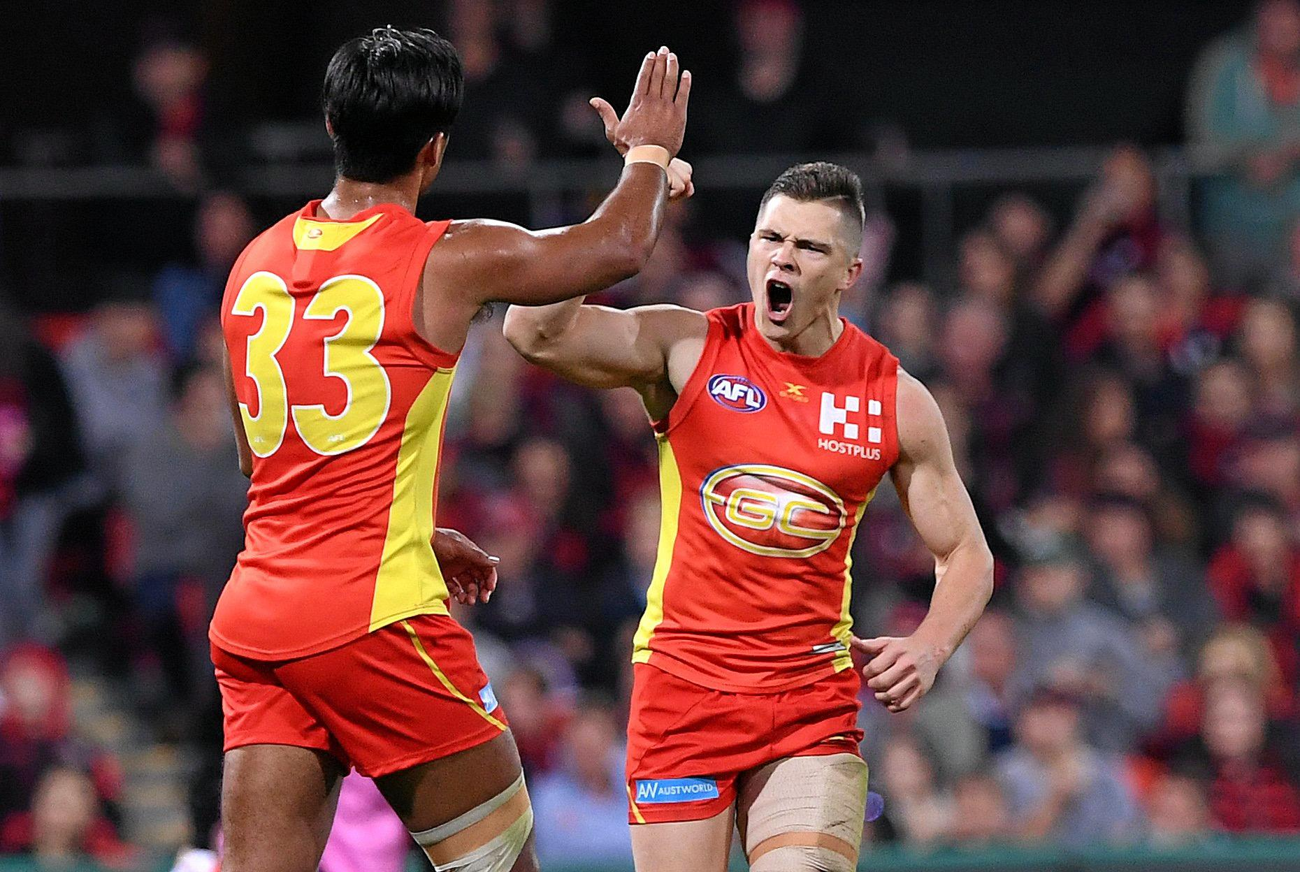 Gold Coast Suns player Ben Ainsworth (right) celebrates after kicking a goal against Essendon in round 22 last season.