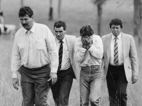 Head in hands, Mick Murphy accompanies detectives led by Ian 'Speed' Kennedy through the paddock at Reen Road, Prospect where he raped and murdered Anita Cobby.