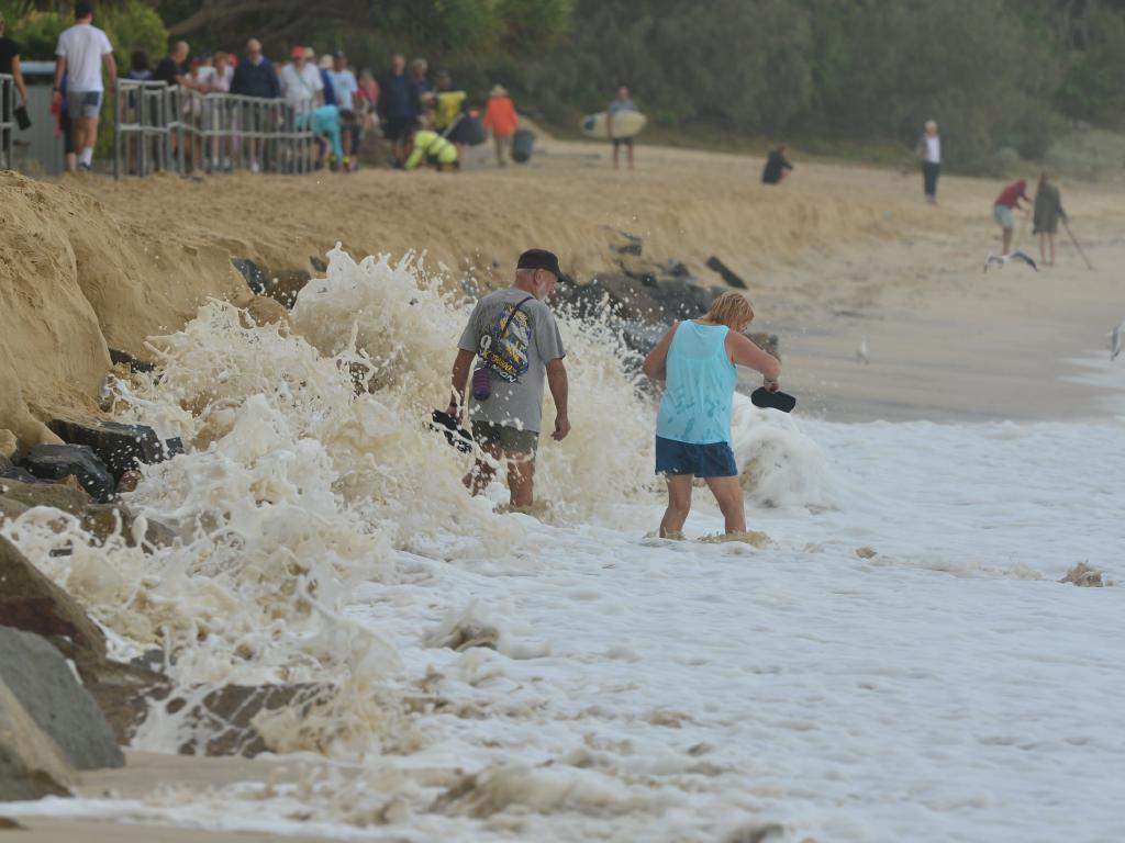 People try to walk down Noosa Main beach on Friday morning. Picture: John McCutcheon