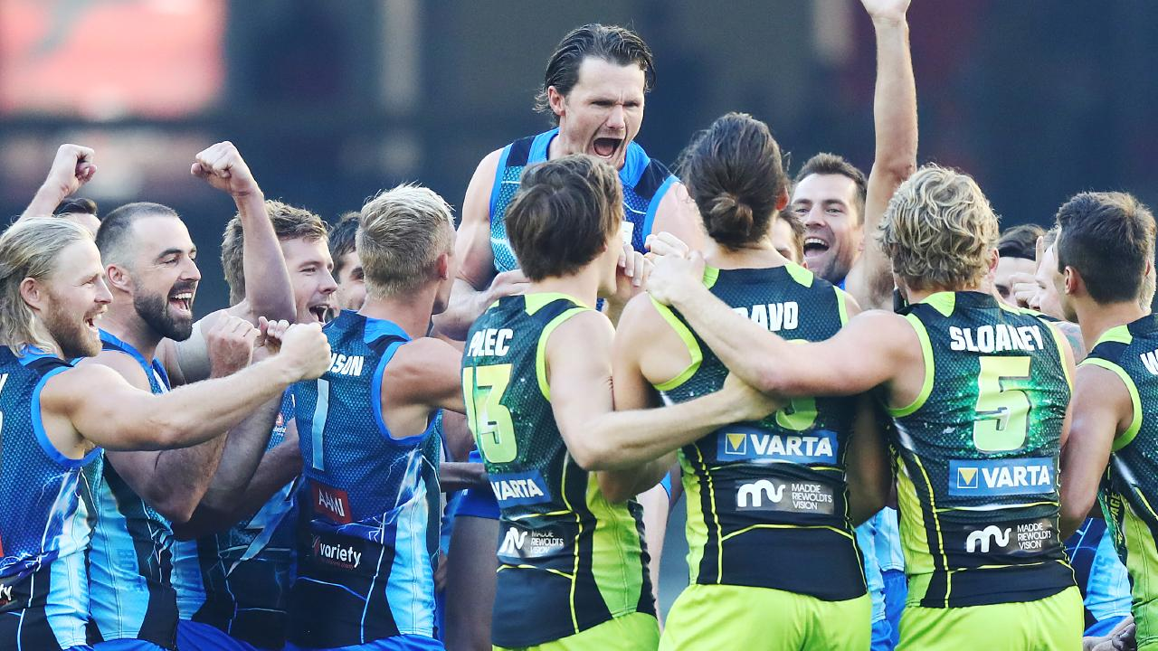 Patrick Dangerfield and his teammates are animated after winning rock-paper-scissors to decide the choice of ends. Picture: Getty Images