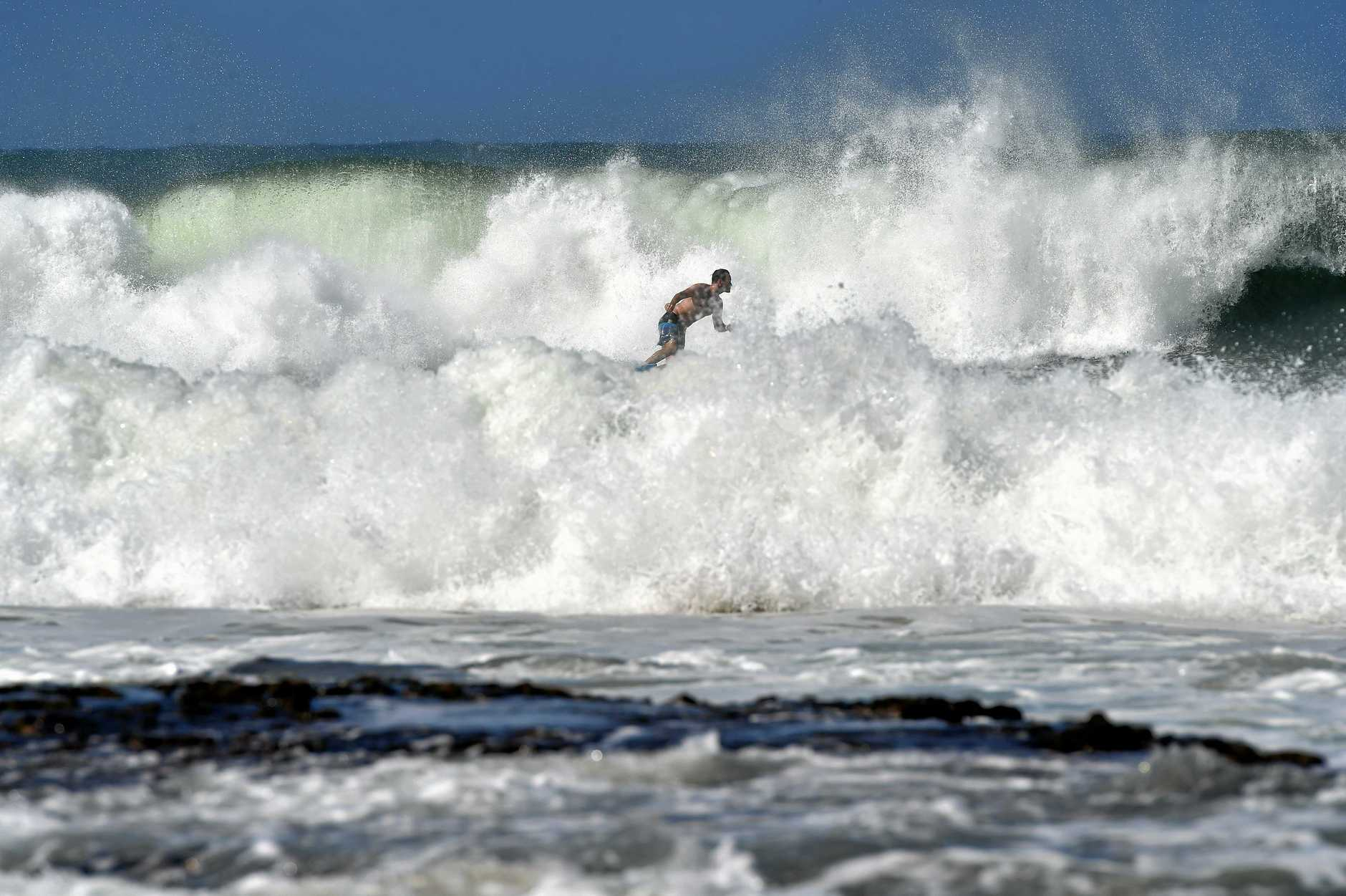 Surfers enjoy the large swell off Mooloolaba Beach from Cyclone Oma.