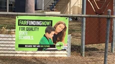 Corflutes on the fence at Biloela State School promoting the Fair Funding Now! campaign