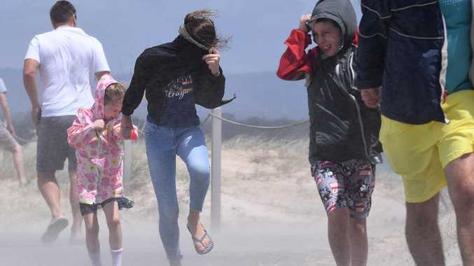 People struggle with blowing sand and high winds on the Gold Coast. Huge swells and high tides are pummelling southeast Queensland beaches. Picture: AAP Image/Dave Hunt
