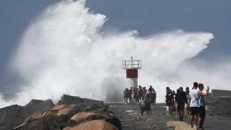 People at The Gold Coast Seaway as Cyclone OMA whips up wild conditions. Picture: Jason O'Brien