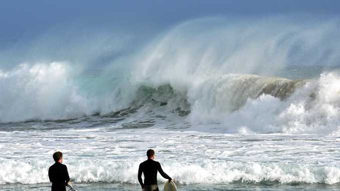 MOVING NORTH: Surfers watch on as the giant swell from Cyclone Oma hits Snapper Rocks.