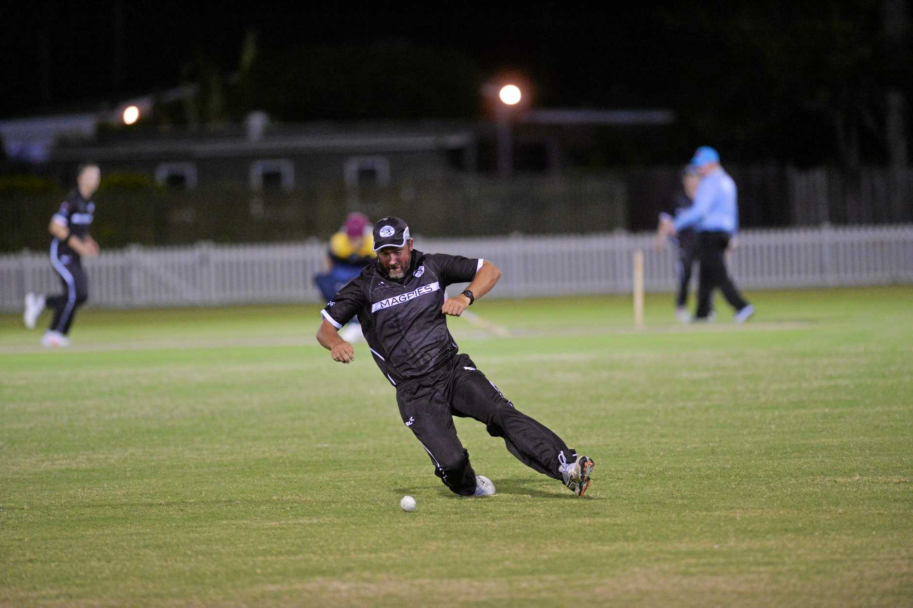 A magpies fielder makes a slide to stop a ball bound for the boundary.
