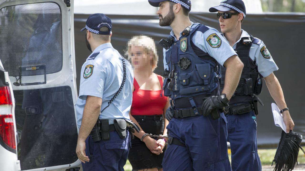 A woman seen in handcuffs outside the Ultra Australia festival at Parramatta Park yesterday. Picture: Damian Shaw