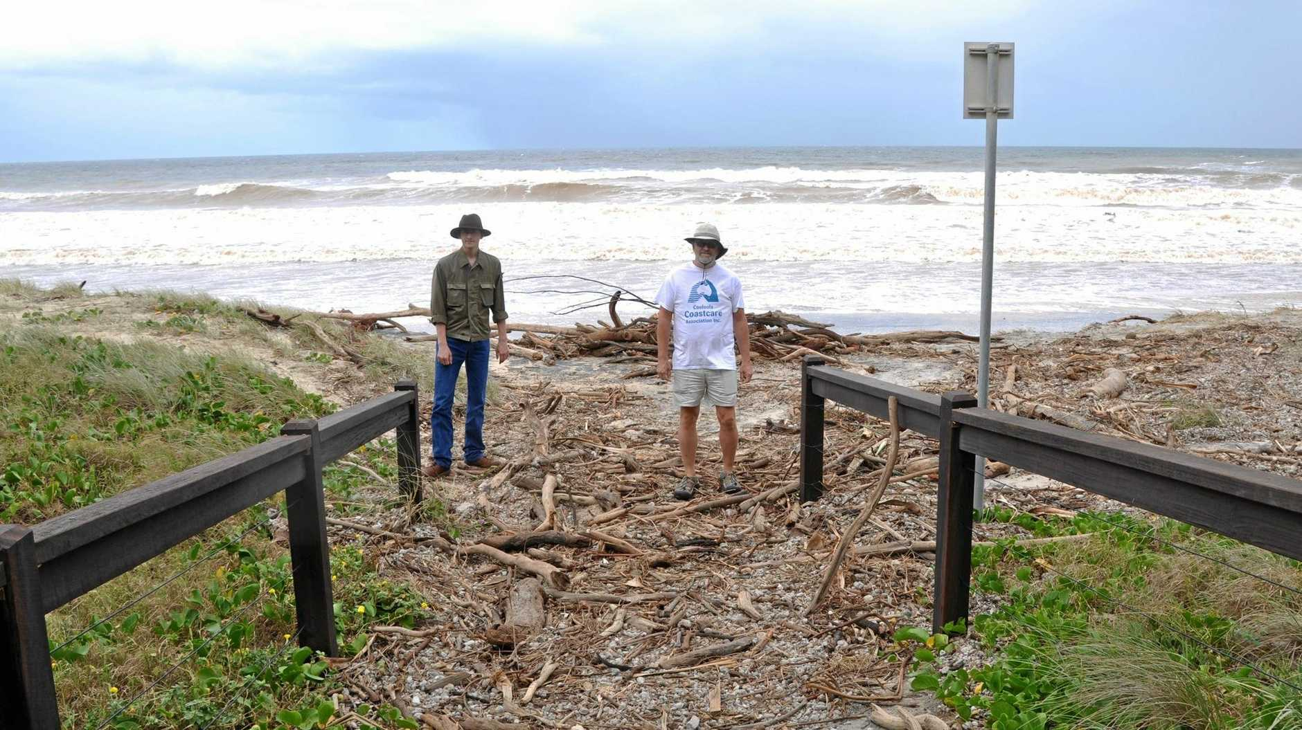 BIG LOSS: Randy Orwin, president of Cooloola Coastcare and his son Hagen Orwin assess damage at Rainbow Beach yesterday.