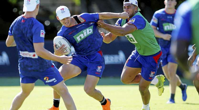 Kalyn Ponga is tackled by Herman Ese'ese during a Knights training session in Newcastle on Tuesday morning.