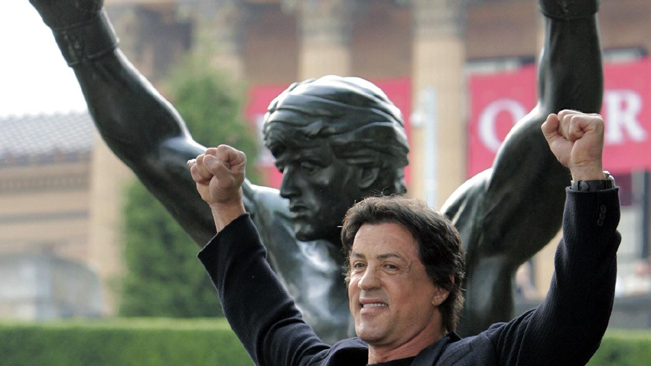 Sylvester Stallone poses in front of the bronze statue of Rocky Balboa.