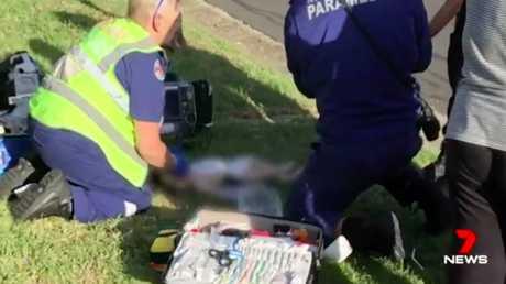 The child lay lifeless on the grass along a Lurnea street. Source: 7News