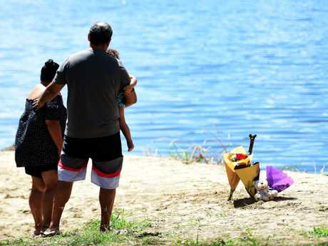 Townsville locals stand where the brothers were found in the Ross River. Picture: Alix Sweeney