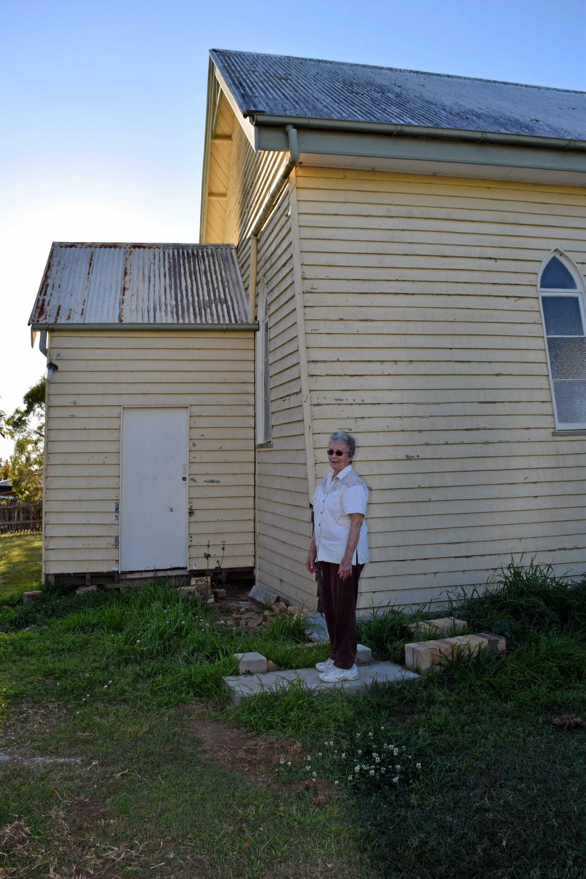Tiaro parishioner Sybil Medew stands where the side door to the Uniting Church used to be before a freak tornado blew the building 12 feet off its stumps.