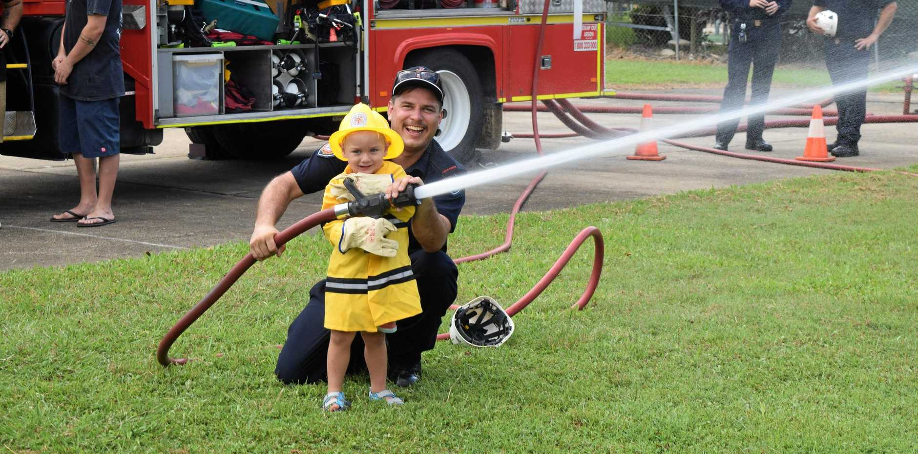 TOO CUTE: Future firefighter Abel Vuk was chuffed when firefighter Dave Gibson showed him the ropes.
