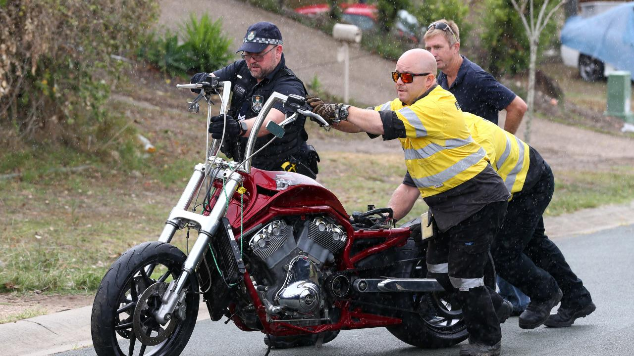 A motorcycle is taken from the scene at Kumnick Street, Upper Coomera where there was a shooting last night involving a Rebels bikie Gokhan Turkyilmaz. Pics Adam Head