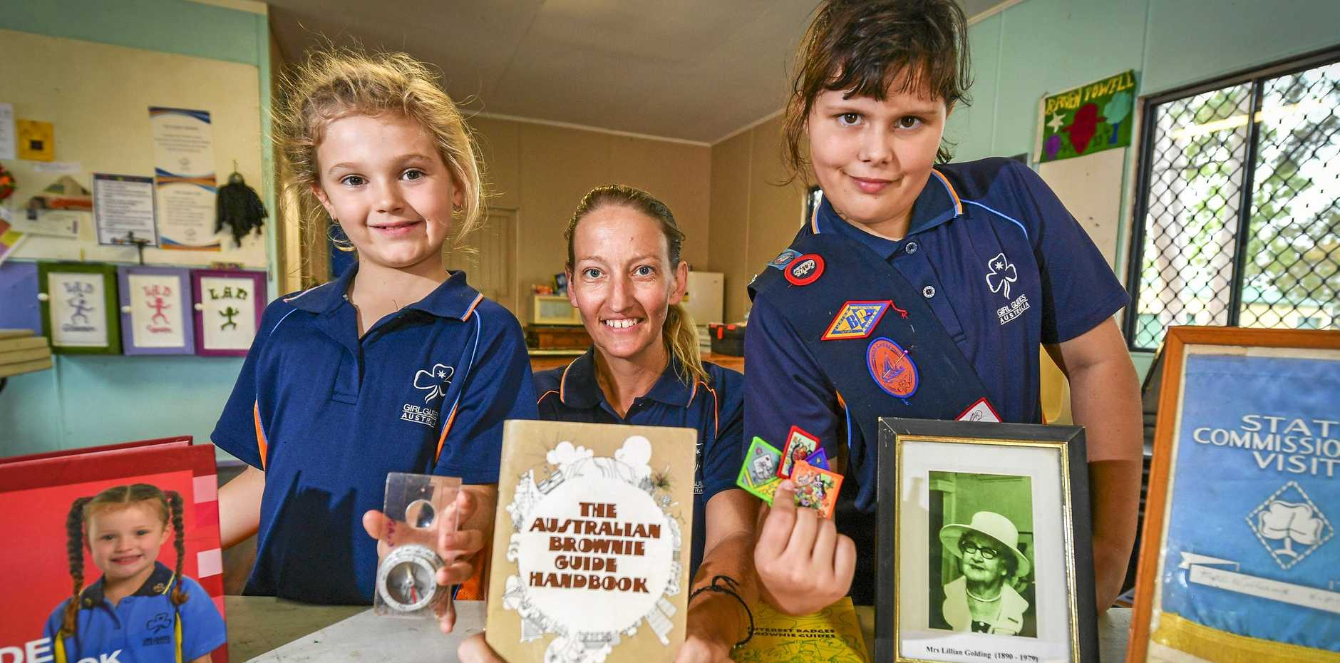 Gladstone girl Guides Poppi Ahern (LEFT) and Tamsin Roberts (RIGHT) with co-unit leader Donna Ellis as the QueenslandGirl Guides celebrate their centenary.