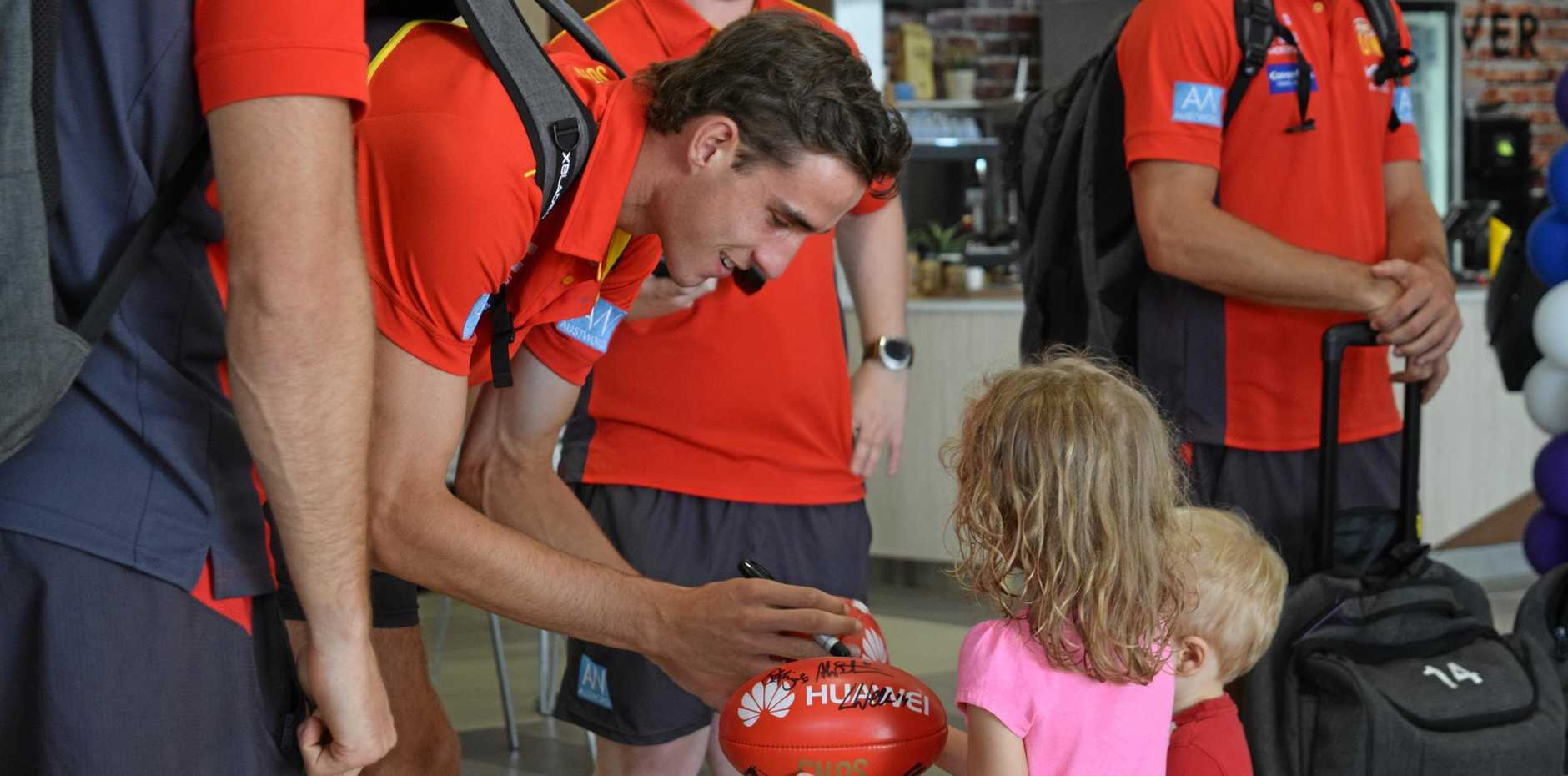 Cold Coast Suns player Ben King signs an AFL ball for Olivia and Tyler Webber at Mackay Regional Airport.