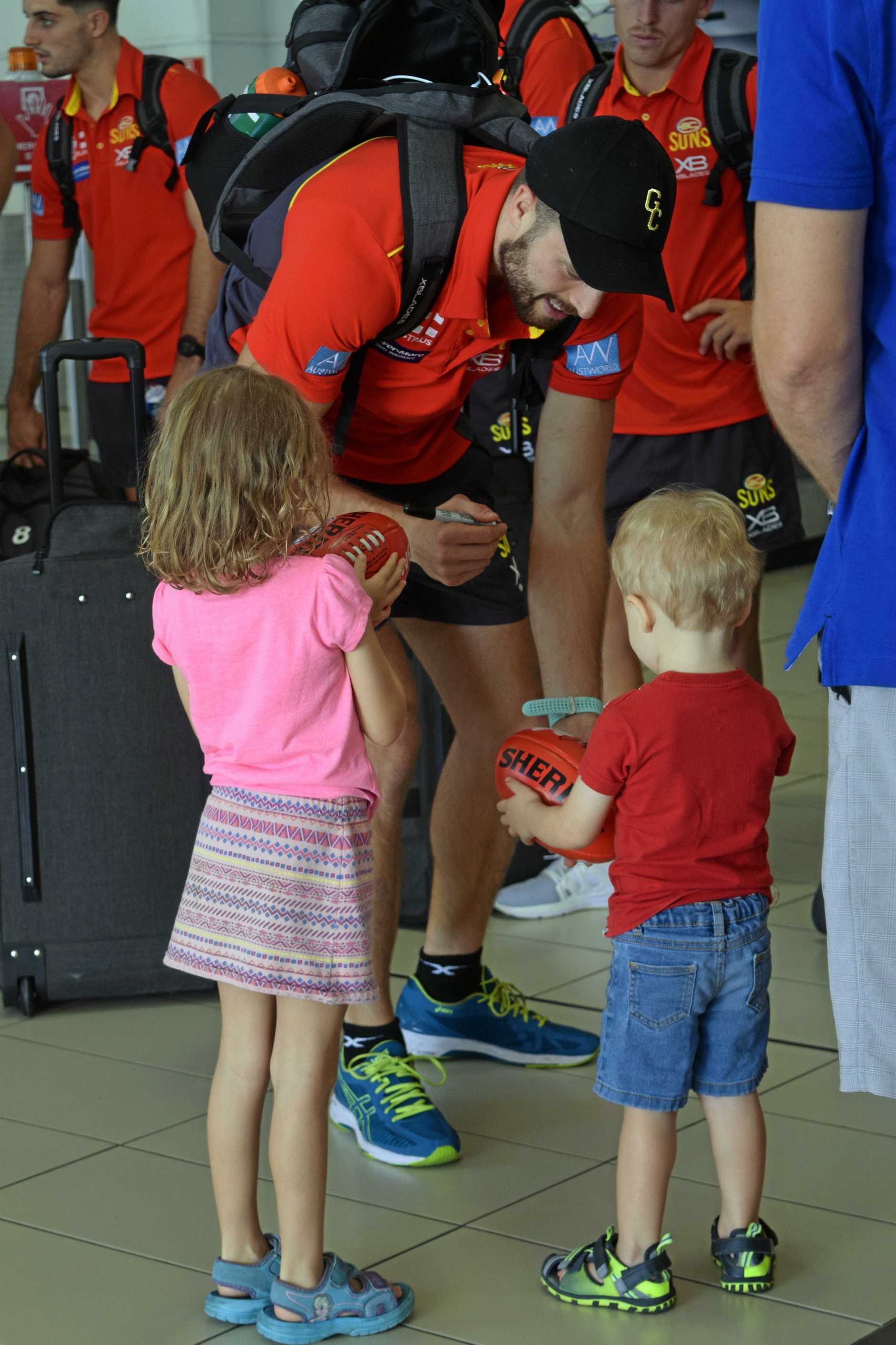 Pearce Hanley signs an AFL ball for Olivia and Tyler Webber at Mackay Regional Airport.