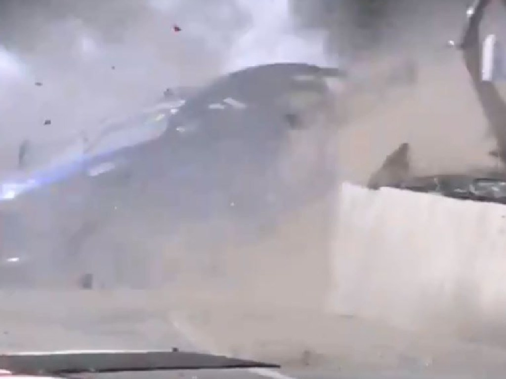 Macauley Jones hits the wall backwards as his car comes apart in a cloud of dust.