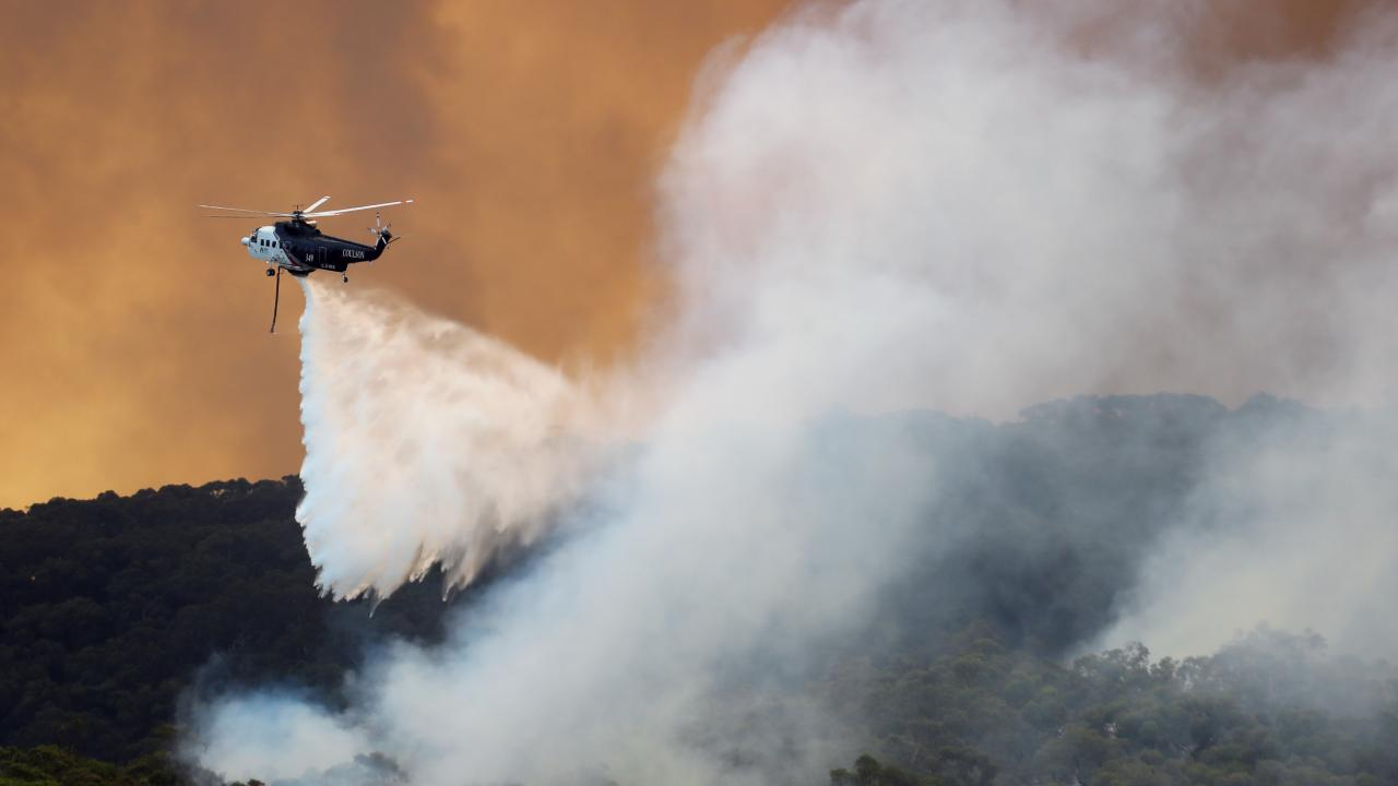 A helicopter douses the flames in Bunyip State Park. Picture: Alex Coppel