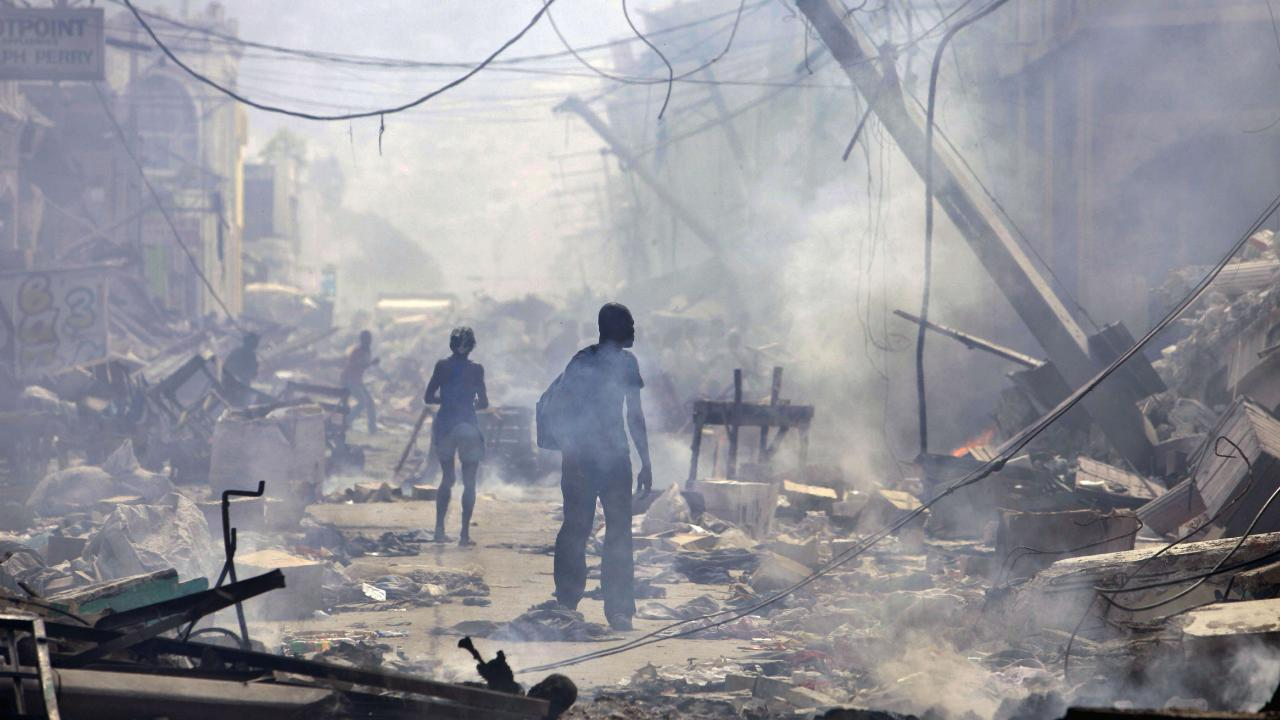People walk down a street amid earthquake rubble in Port-au-Prince. Picture: Gregory Bull