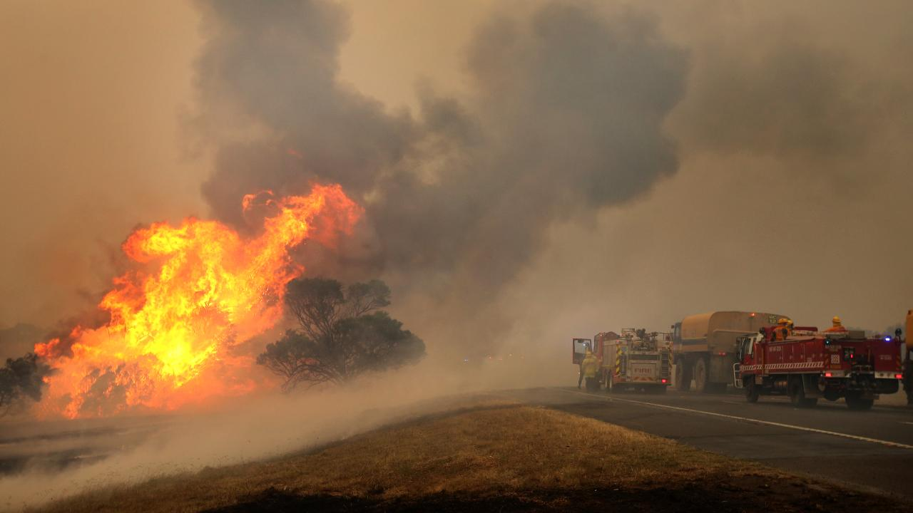 Firefighters desperately try to stop the Bunyip state forest bushfire crossing the Princes Freeway. Picture: Stuart McEvoy/The Australian
