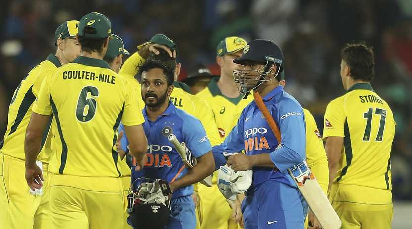 Australian cricketers congratulate India's Mahendra Singh Dhoni, right in blue, and Kedar Jadhav after the Indian team won the first one day international.