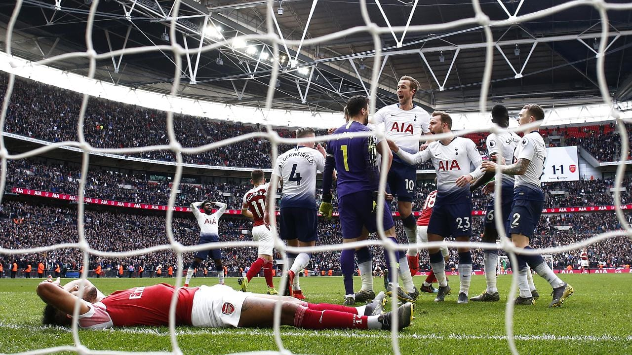 Hugo Lloris of Tottenham Hotspur celebrates with Harry Kane and teammates after saving a penalty.