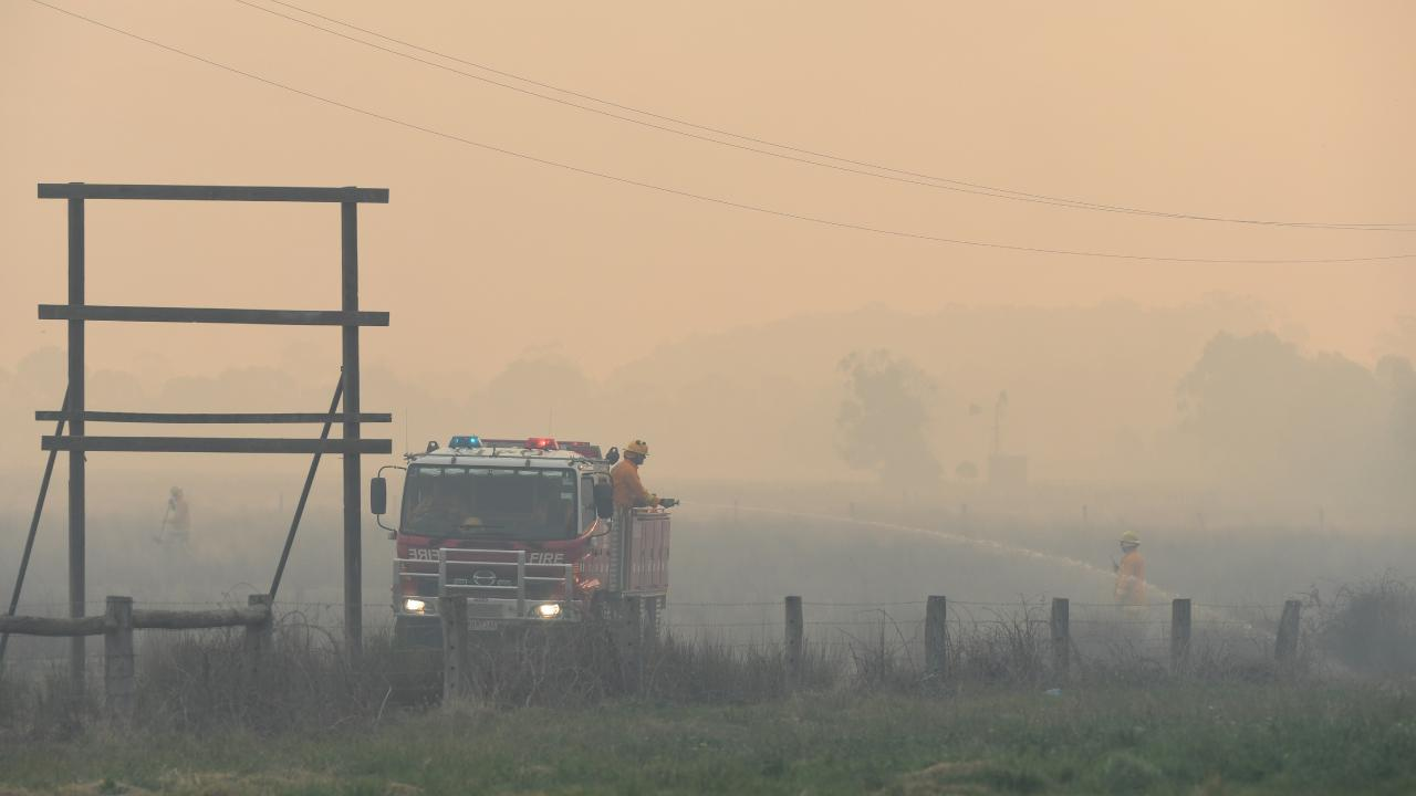 A CFA crew extinguishes a spot fire on the Bunyip side of the Princes Highway in Victoria. Picture: AAP Image/James Ross