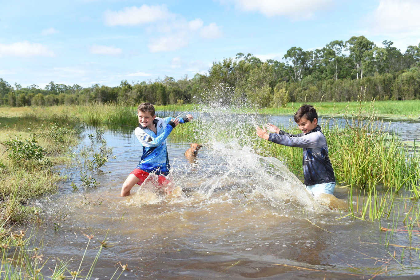 Lachlan,8, and Hunter,10, McLean having fun in one of the lagoons at Susan River Homestead where 12 months ago they were rescueing fish from muddy puddles.