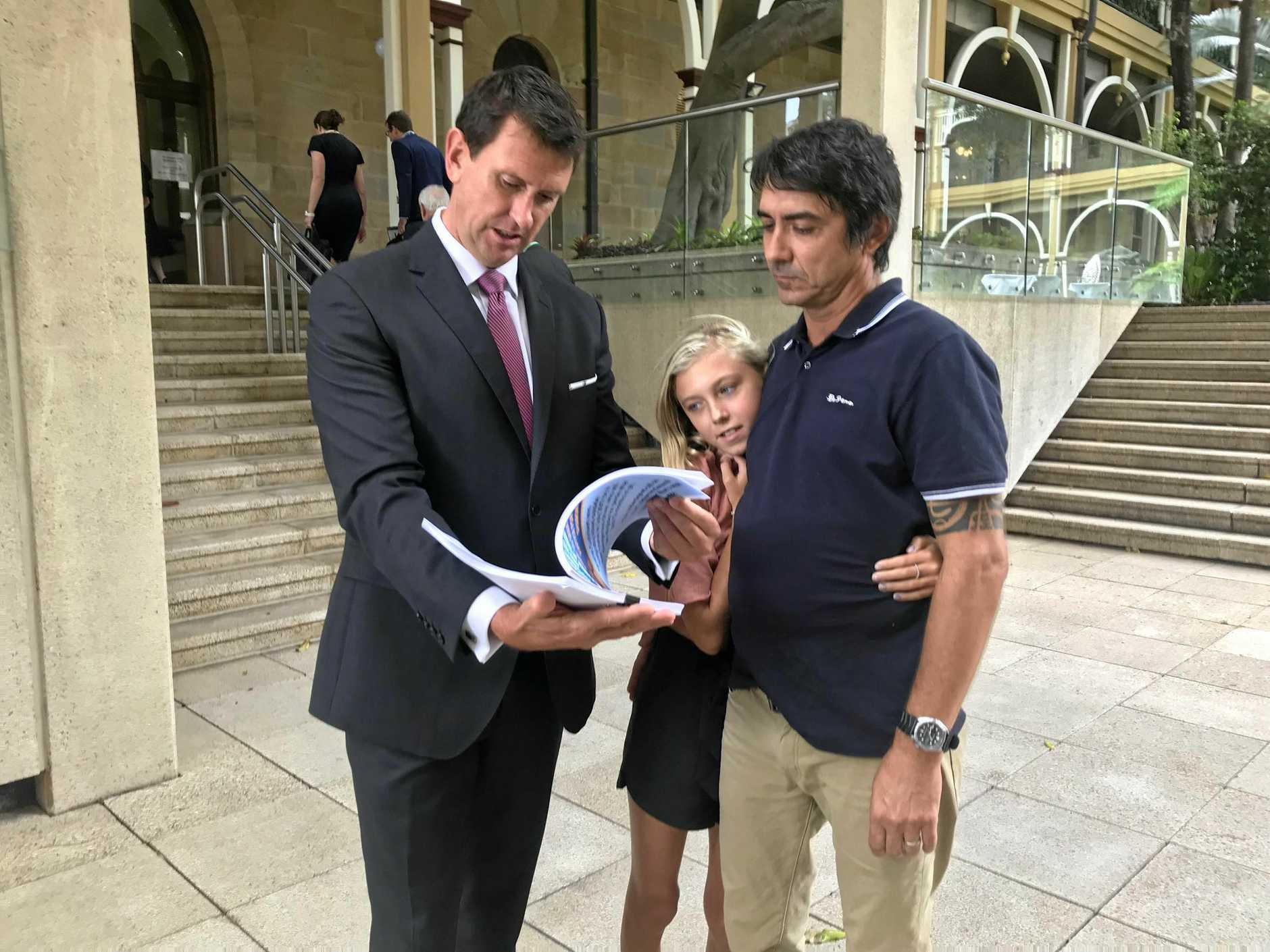 Member for Ninderry Dan Purdie peruses a petition with Coolum dad Michael Cuthbert and his daughter Makayla Cuthbert calling for an appeal against Andrew David Muirhead's sentence.