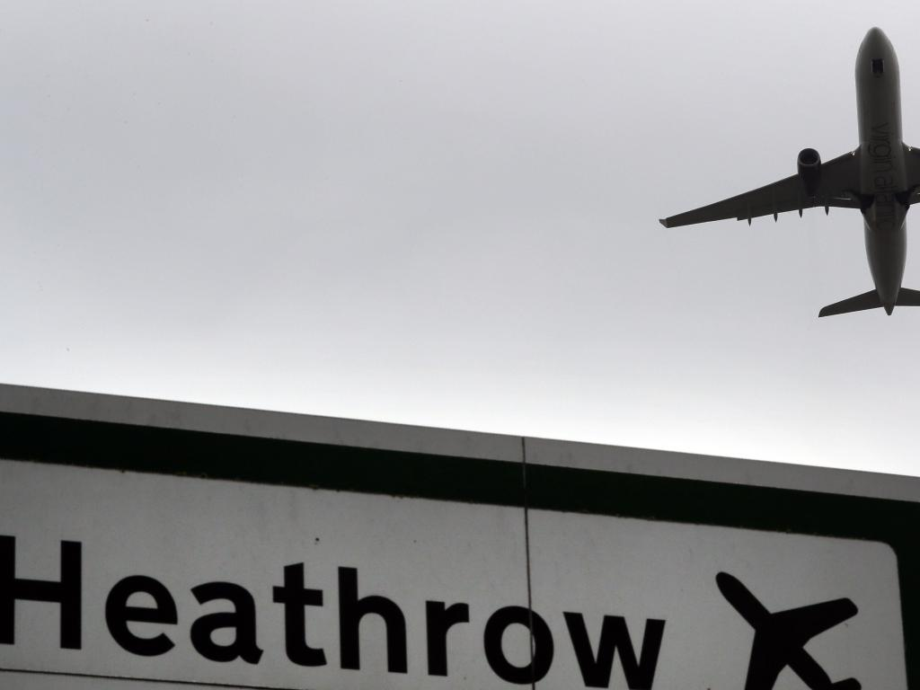 A plane takes off over a road sign near Heathrow Airport in London. Picture: AP
