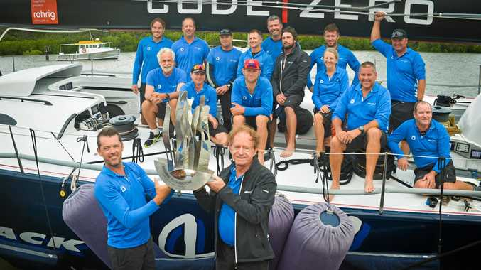 VICTORY: Skipper Mark Bradford and owner Peter Harburg in front of the victorious crew of Black Jack, which broke the Brisbane to Gladstone race record last year.