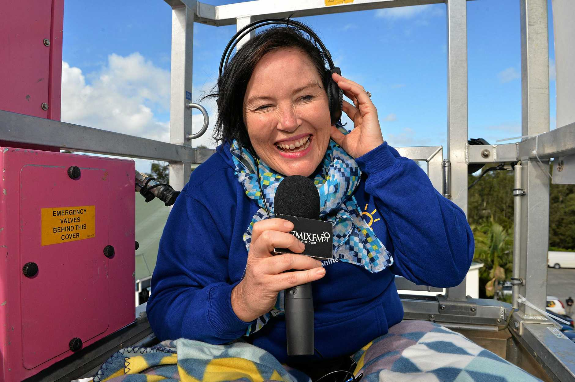 Caroline Hutchinson from MIX FM is raising money for charity by broadcasting from the top of a crane. Photo: Warren Lynam / Sunshine Coast Daily