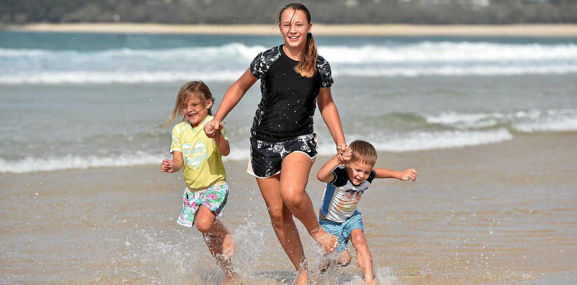 Victorian tourists April, 5, Paige, 13, and Taylor Marcroft, 3, enjoy a splash at Mooloolaba Beach.