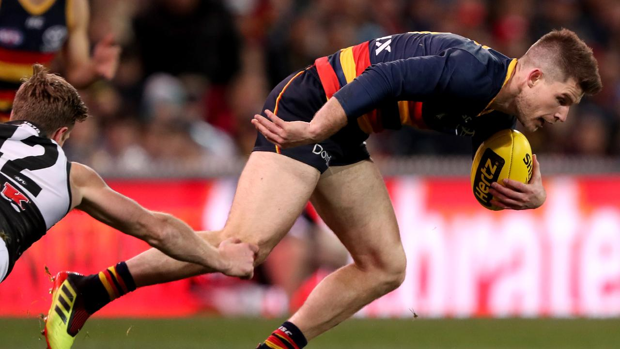Crows  Bryce Gibbs is tackled by Port Adelaide's Tom Jonas at the Adelaide Oval. Picture: James Elsby/Getty
