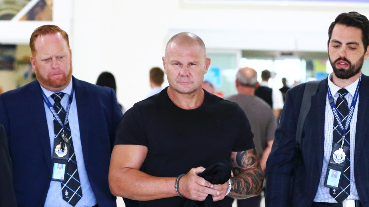 Broadbeach bikie brawl identity Jason 'JT' Trouchet being walked out of Gold Coast Airport by cops after being extradited from NSW on drug trafficking charges. *** NO BYLINE ***