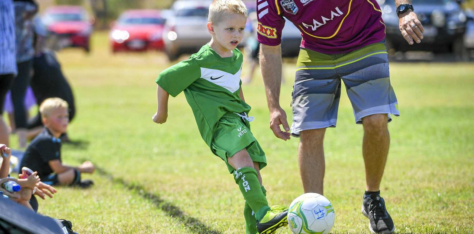 Clinton Football Club's Dean gets some help with a kick in against Calliope Football Club in their Under 7's match at Palm Drive Fields.
