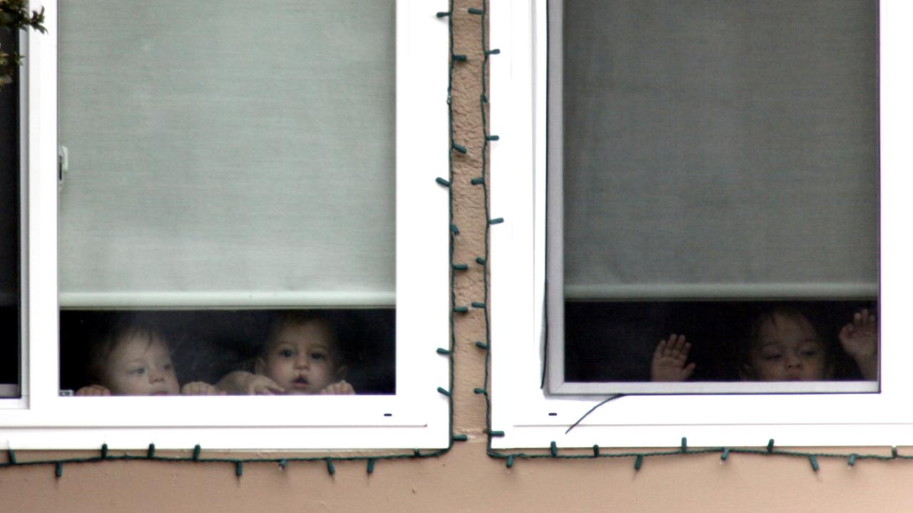 Unidentified children peer from a window in Nadya Suleman's home on the day of the octuplets' first birthday in 2010. Picture: Nick Ut