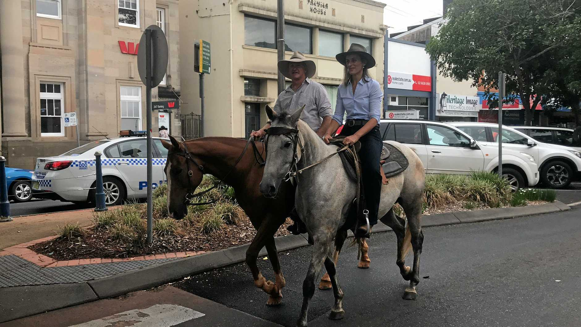 Greens candidate for Lismore Sue Higginson rides into the CBD alongside climate change activist Glenn Morris ahead of pre-polling.