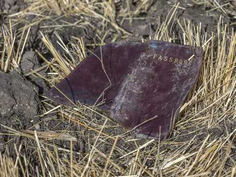A passenger's passport lies on the ground at the scene of the crash. Picture: AP
